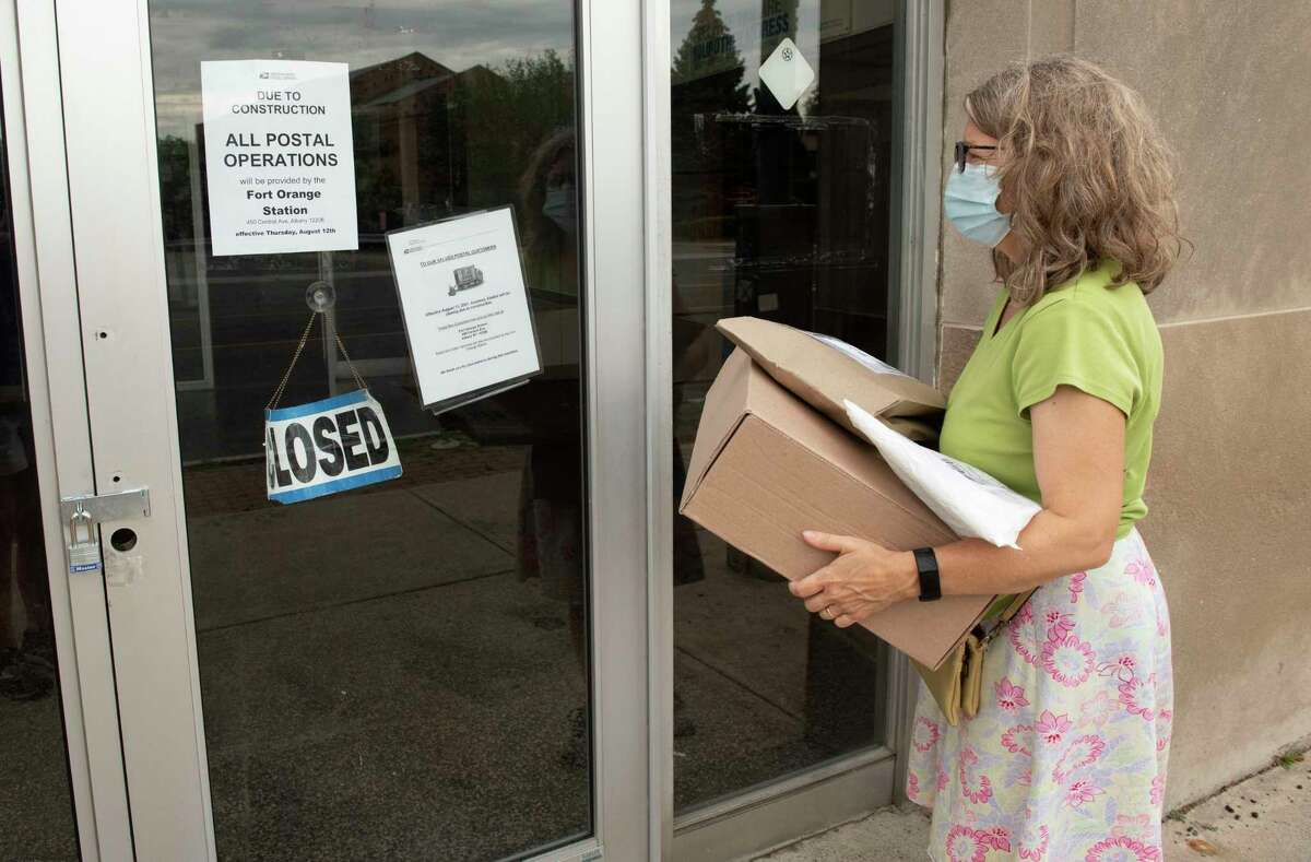 Nancy Perini of Albany sadly reads the signs posted on the door of the closed post office at 563 New Scotland Ave. on Wednesday, Aug. 18, 2021 in Albany, N.Y. She was hoping to get to the post office before it closed and was surprised to see it my be closed for good.