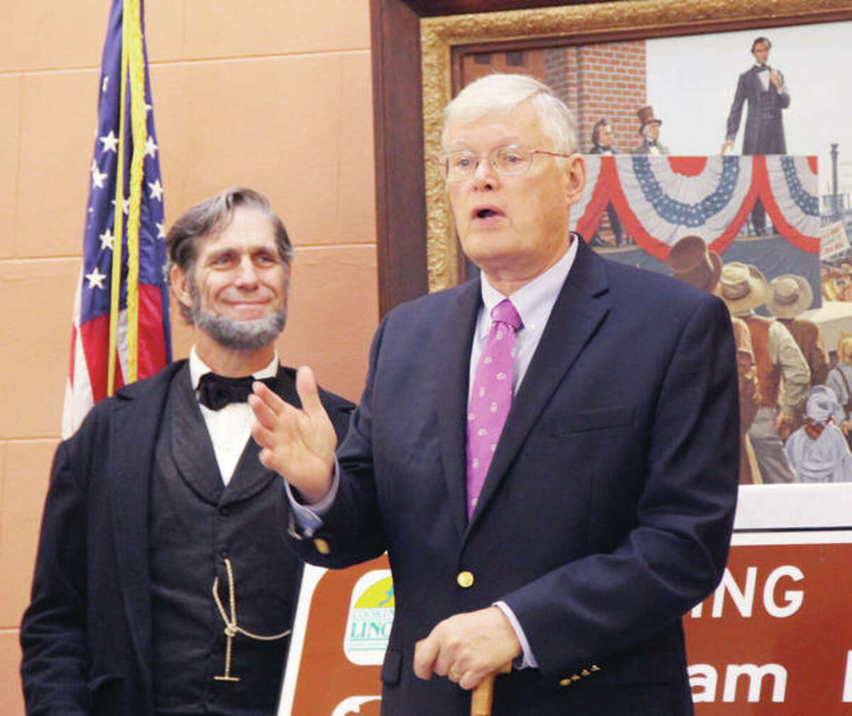 Then-State Sen. Bill Haine talks about the history of Abraham Lincoln and the abolitionist movement in Alton as Lincoln impersonator Randy Duncan, of Carlinville, looks on in October 2016. Behind them is a painting showing a younger Lincoln at the Lincoln-Douglas Debate in Alton. Officials were at City Hall to announce the inclusion of Alton as one of six Gateway Cities to the Abraham Lincoln National Heritage Area in Illinois.