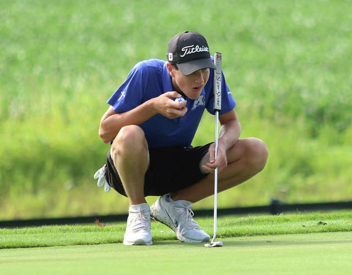 Marquette Catholic junior Aidan O'Keefe lines up a putt before placing the ball during the Hickory Stick Invite on Monday at Belk Park in Wood River.