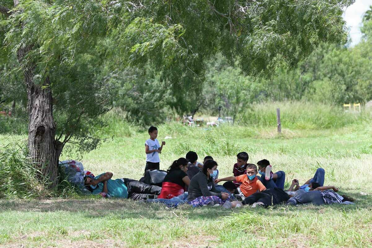 Migrant families take shelter from the sun under the shade of a mesquite tree near a baseball field in La Joya, Texas, in August as they wait for transportation after turning themselves into U.S. Border Patrol agents.