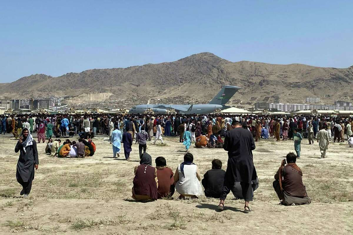 Hundreds of people gather near a U.S. Air Force C-17 transport plane at a perimeter at the international airport in Kabul, Afghanistan, Monday, Aug. 16, 2021.