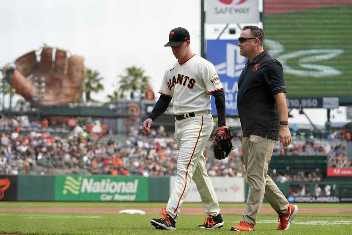 San Francisco Giants starting pitcher Anthony DeSclafani, left, walks off the field with trainer Dave Groeschner during the second inning of a baseball game between the Giants and the New York Mets in San Francisco, Wednesday, Aug. 18, 2021. (AP Photo/Jeff Chiu)