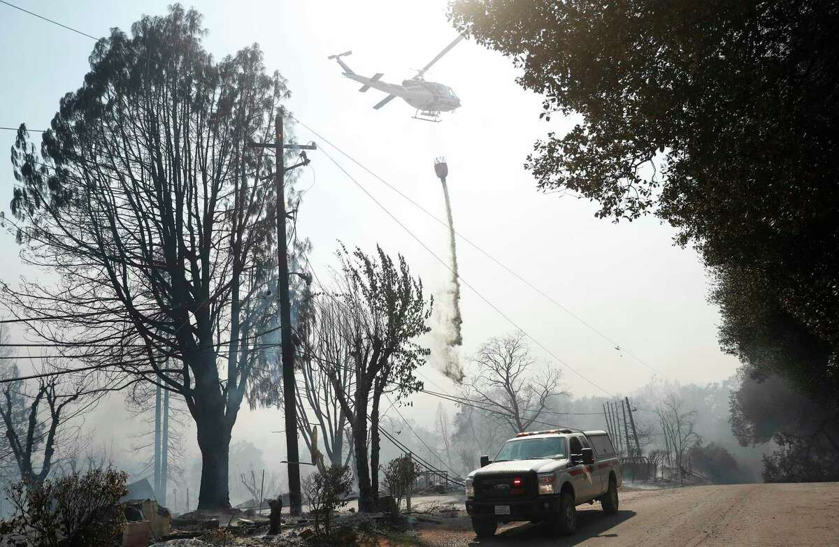 A helicopter makes a water drop along Dam Road during Cache Fire in Clearlake, Calif., on Wednesday, August 18, 2021.