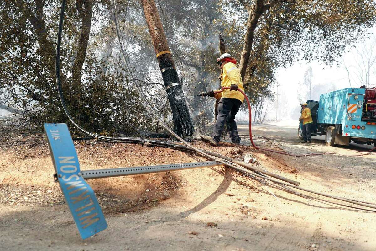 PG&E's Juan Lopez hoses down an electric pole on Wilkinson Road during Cache Fire in Clearlake, Calif., on Wednesday, August 18, 2021.