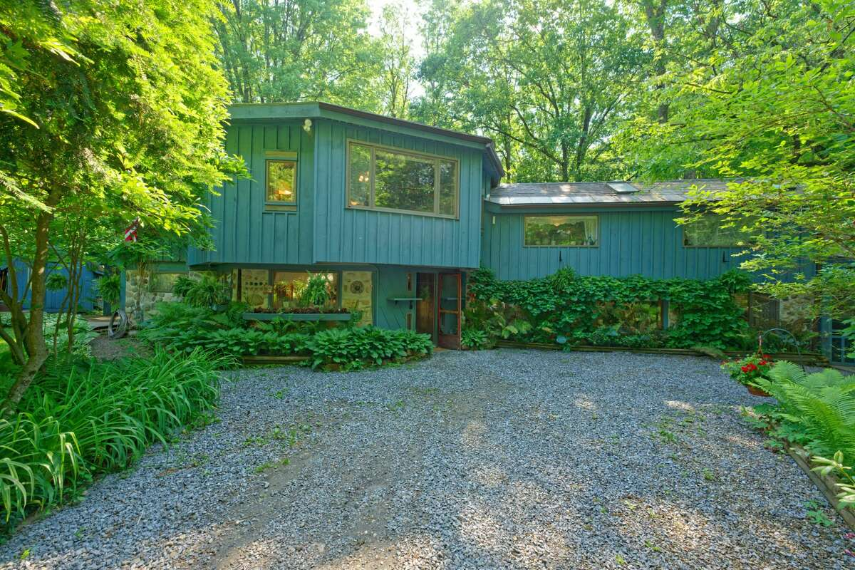 """Listing descriptions for houses are like the contents lists on food from the grocery store. When """"unique"""" is the first ingredient, you know the place has it in abundance. The week's house at 110 Brown Point Lane in the town of Saratoga was built by the current owner in 1989. She collected stones from property her father owned, hand-mixed the cement and built the original, octagonal portion of the 2,153-square-foot house herself. Before the last wall was built, her brother drove a tractor inside and installed the center beam. The 7.5-acre property has 90 feet of waterfront along Fish Creek. It is lush this time of year with perennial plants. The house has three bedrooms and two bathrooms. A second two-story building has parking for two cars and the second floor could be made over into a studio or in-law apartment. Schuylerville schools. List price: $428,800. Taxes: $7,751. Contact listing agent Jennifer Vucetic of Exit Realty Empire Associates at 518-879-6318."""