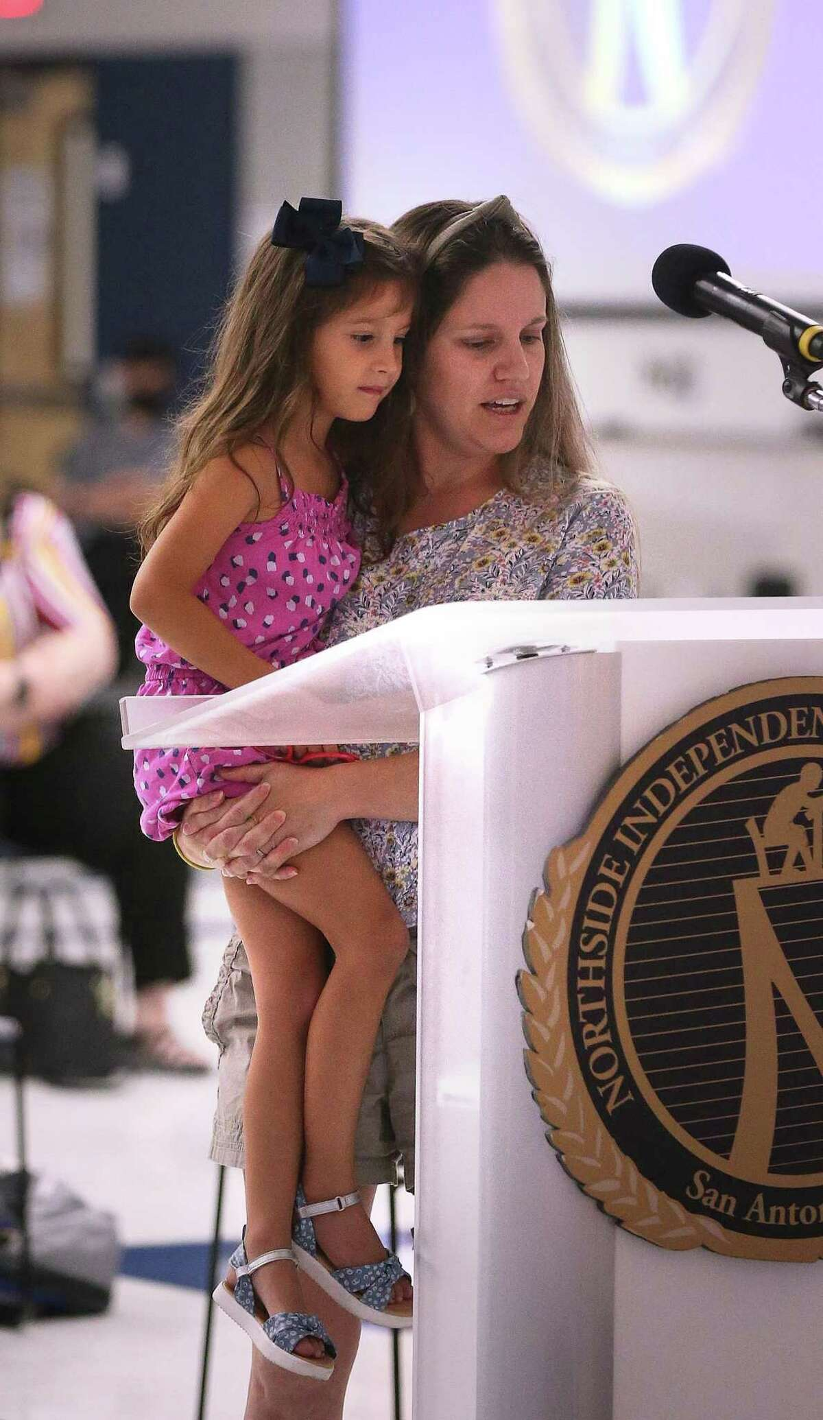 At Northside ISD's board meeting, Lesley Casias reads with her daughter Irelynn, 5, the letter she wrote last night on why they should not mandate wearing a mask.