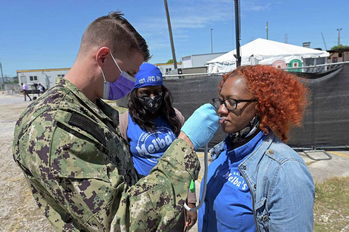 Hospital Corpsman 2nd Class Cameron King, left, checks the temperature of Ralinda Guss from Melba's Poboys, who donated food to support Army North's work helping with the city's pandemic response in April, 2020. After ending thousands of similar missions in June, Army North is resuming them and has sent a team to Lafayette, La.