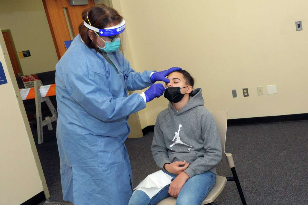 Dr. Susan Glasman administers a COVID-19 test to Luciano Warner, of Meriden, at a testing site on the UConn Stamford campus in January.