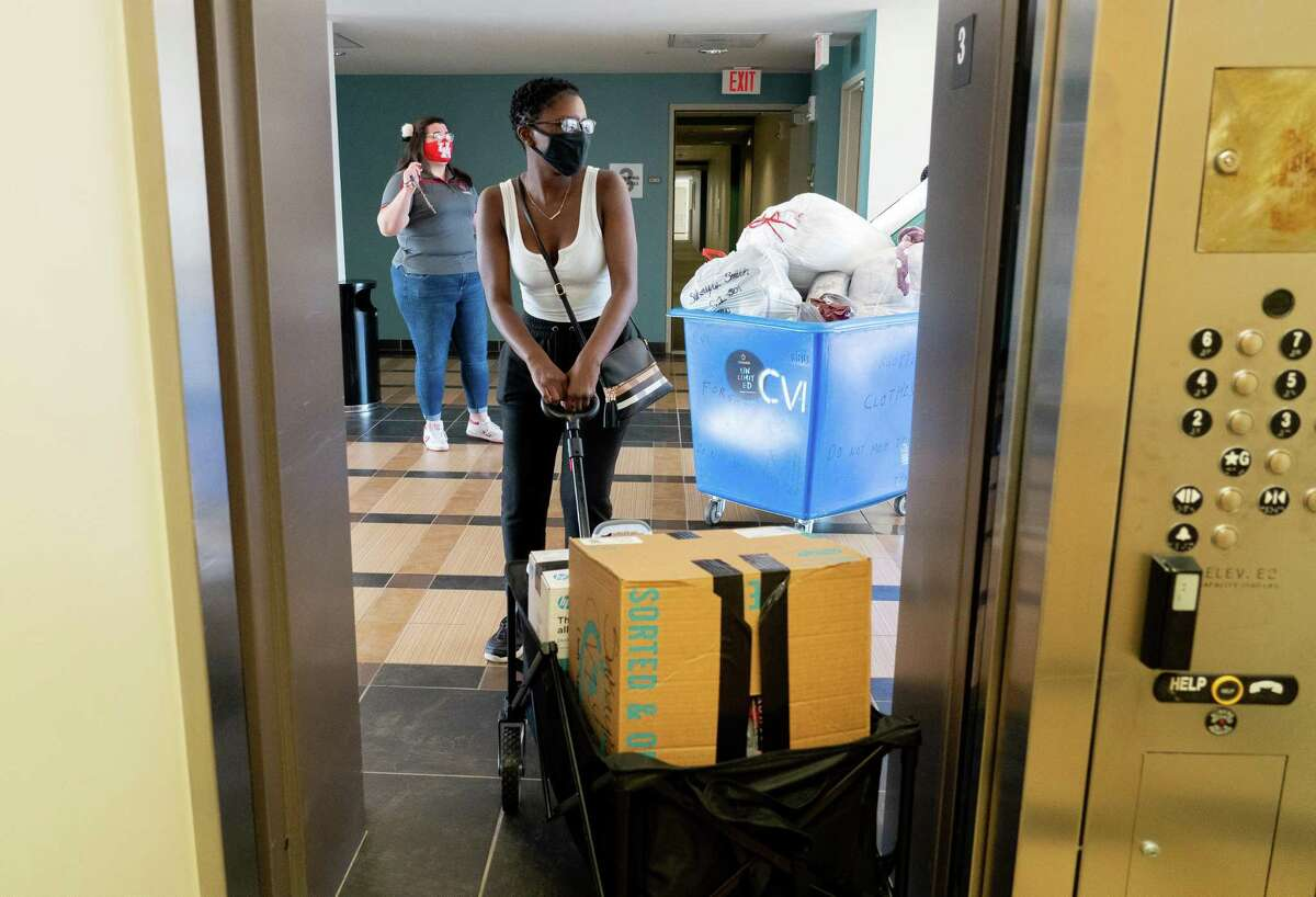Sakayla Smith, center, pulls a cart filled with some of her belongings as she moved into her dorm at the University of Houston on Wednesday, Aug. 18, 2021, in Houston.