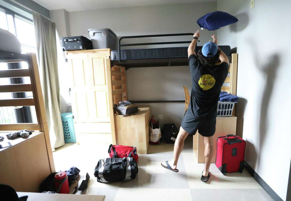 """Nick Cascarano, 19, unpacks in his dorm during """"move-in"""" day at the Guinan Residence Hall on the University of St. Thomas campus, Wednesday, August 18, 2021, in Houston. Cascarano is one of the """"Take 2"""" students returning to campus after the pandemic limited campus life last year."""