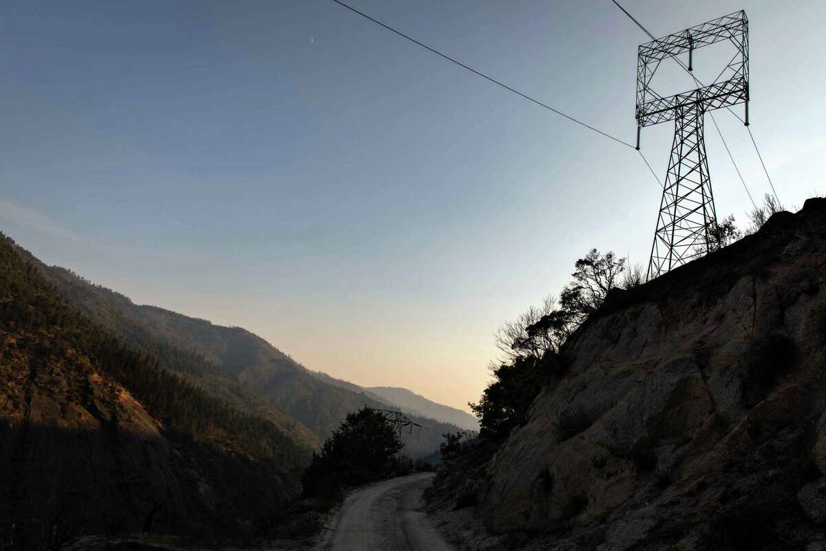 Overhead power lines run across Camp Creek Road, above the North Fork Feather River, in Plumas County, California on Saturday, Aug.14, 2021. Ignited on July 13, the Dixie Fire has been burning for over a month, and has grown to over 650,000 acres.