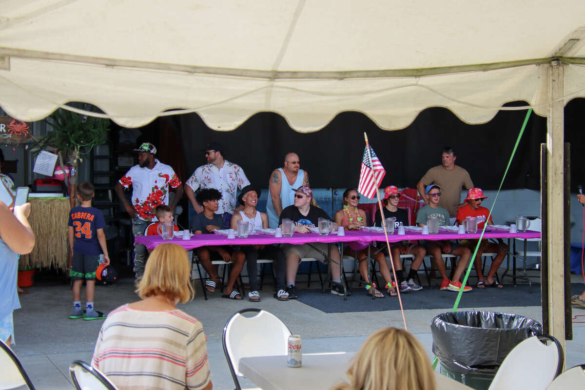 More than one dozen people compete for bragging rights in the cheeseburger eating contest Aug. 18, 2021.
