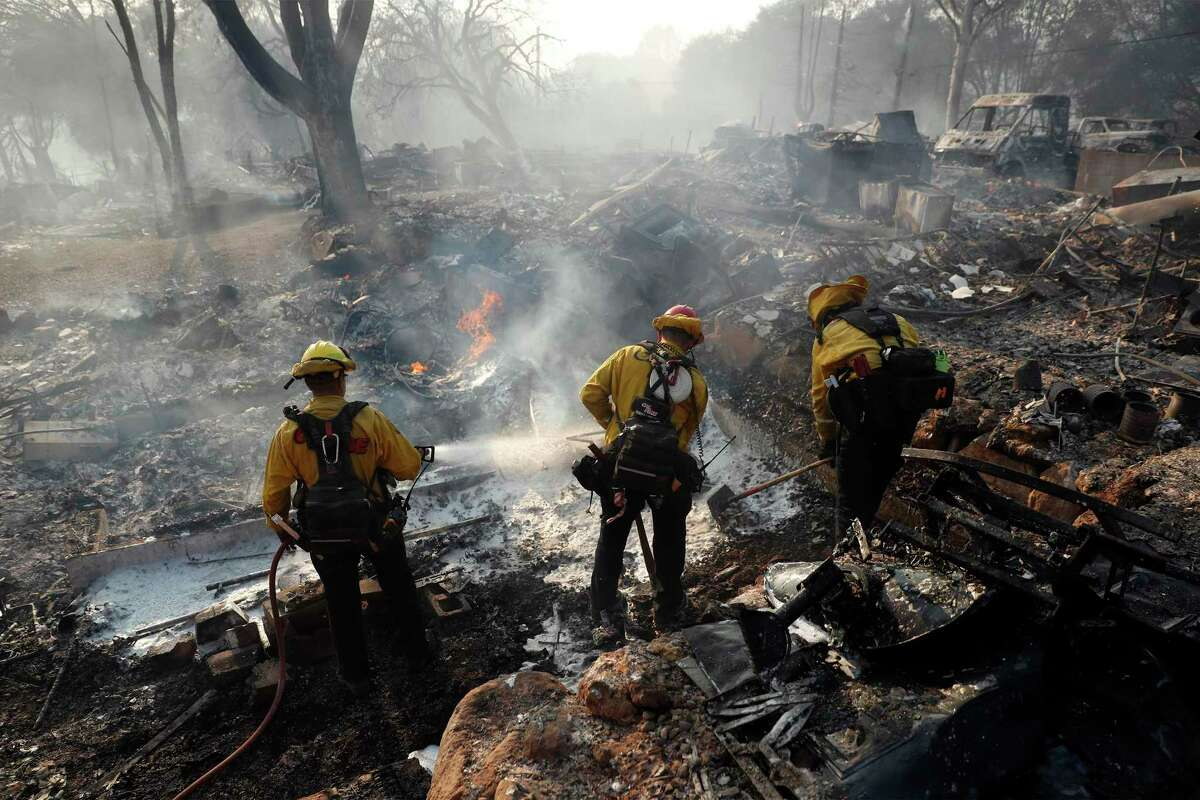 CalFire firefighters extinguish hot spots in the burning rubble at Creekside Mobile Home Park during Cache Fire.