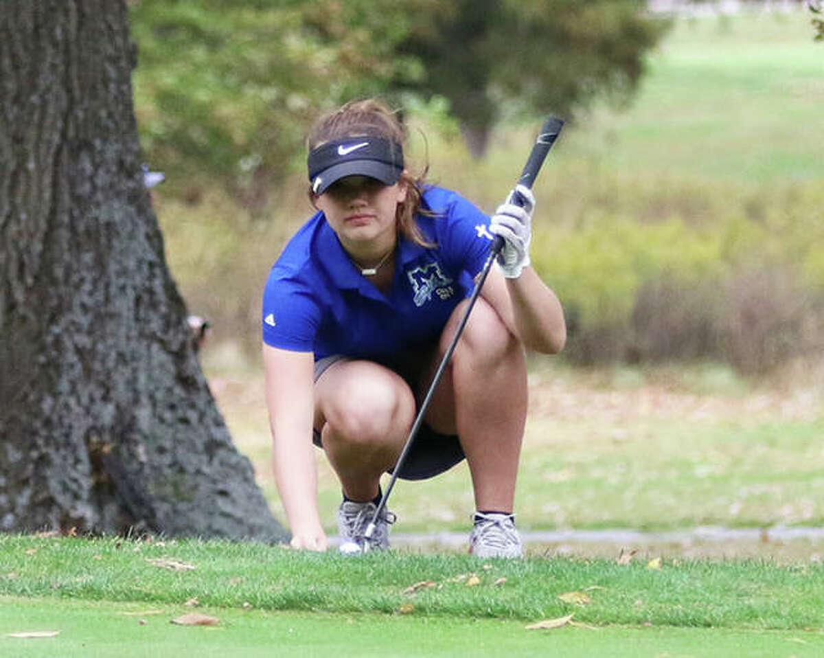 Marquette Catholic's Clancy Maag, shown lining up a putt during the Class 1A sectional at Salem last season, shot a 43 to help the Explorers to dual wins over Alton and Father McGivney on Wednesday at Spencer T. Olin golf course in Alton.