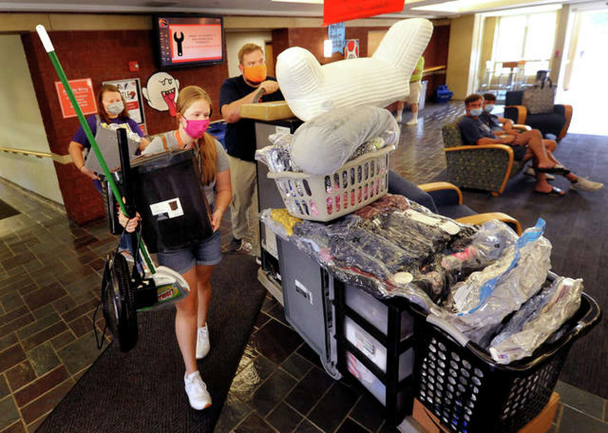 Southern Illinois University Edwardsville Freshman Emily Mutschler, foreground left, of Rushville, carries belongings through the lobby of Bluff Hall at SIUE Wednesday. She gets some help from her parents, Amy and Dave Wiley.