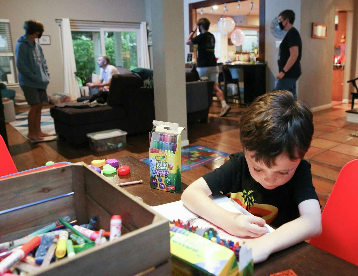 Freddie Pepper, 5, tries out his new school supplies at his Houston home on Wednesday, Aug. 18, 2021. Freddie, along with his twin brother Charlie, will be starting kindergarten this school year. Their older brothers, Cyrus, 15, and August, 17, have already been vaccinated.