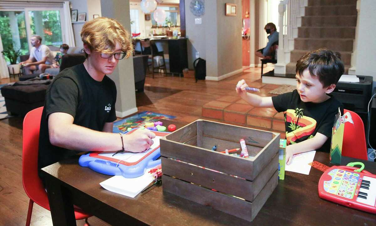 August Pepper, 17, colors with his brother, Freddie, 5, in their in Houston home on Wednesday, Aug. 18, 2021. Freddie, along with his twin brother Charlie, will be starting kindergarten this school year.