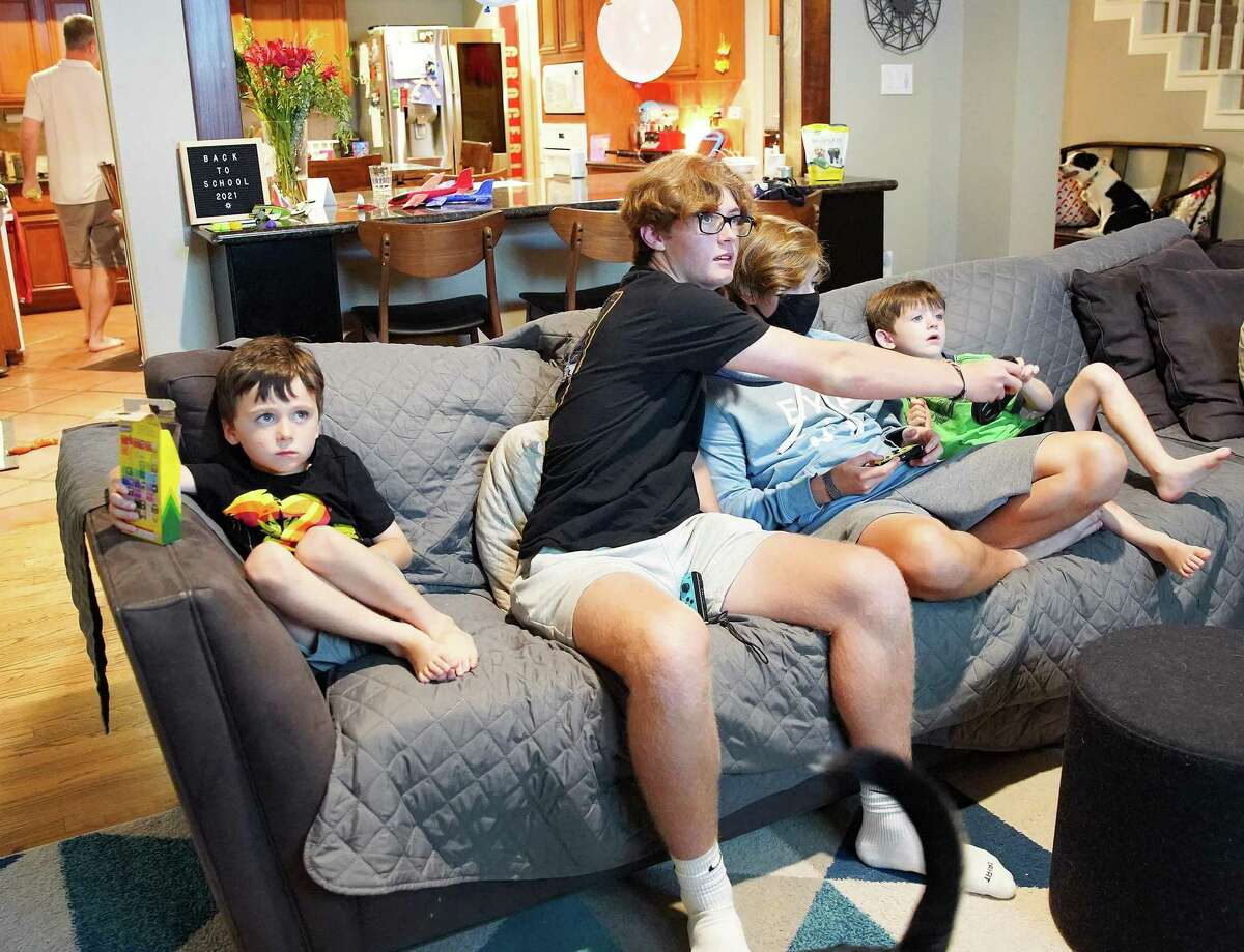Brothers Freddie, 5, August, 17, Cyrus, 15, and Charlie Pepper, 5, play video games in their Houston home on Wednesday, Aug. 18, 2021. The high schoolers are vaccinated, however the family is concerned about the spread of COVID to their young twin boys.