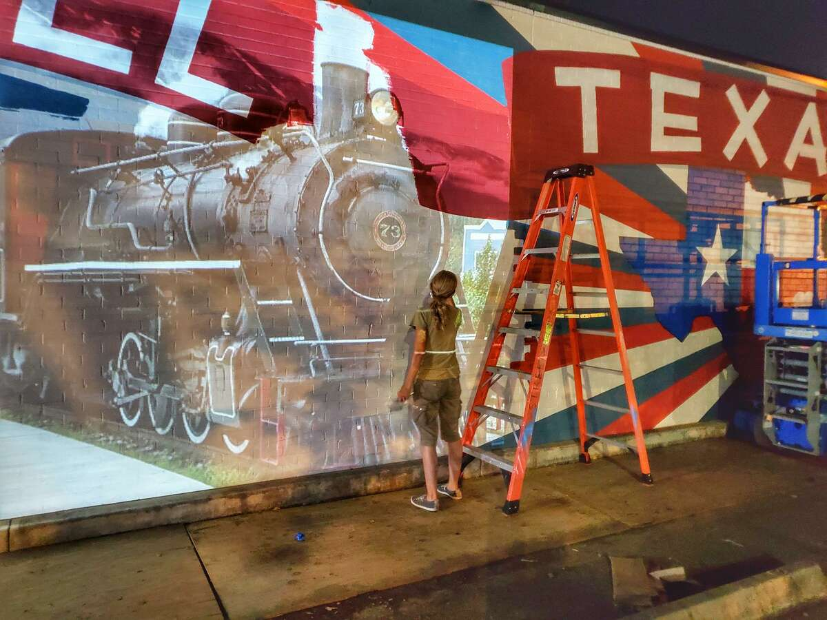 Artist Beth Mankin works into the night when it's cooler to put the final touches on Tomball's first mural art. The project has been delayed several times because of heavy rainfall, but should be finished by the end of the month.