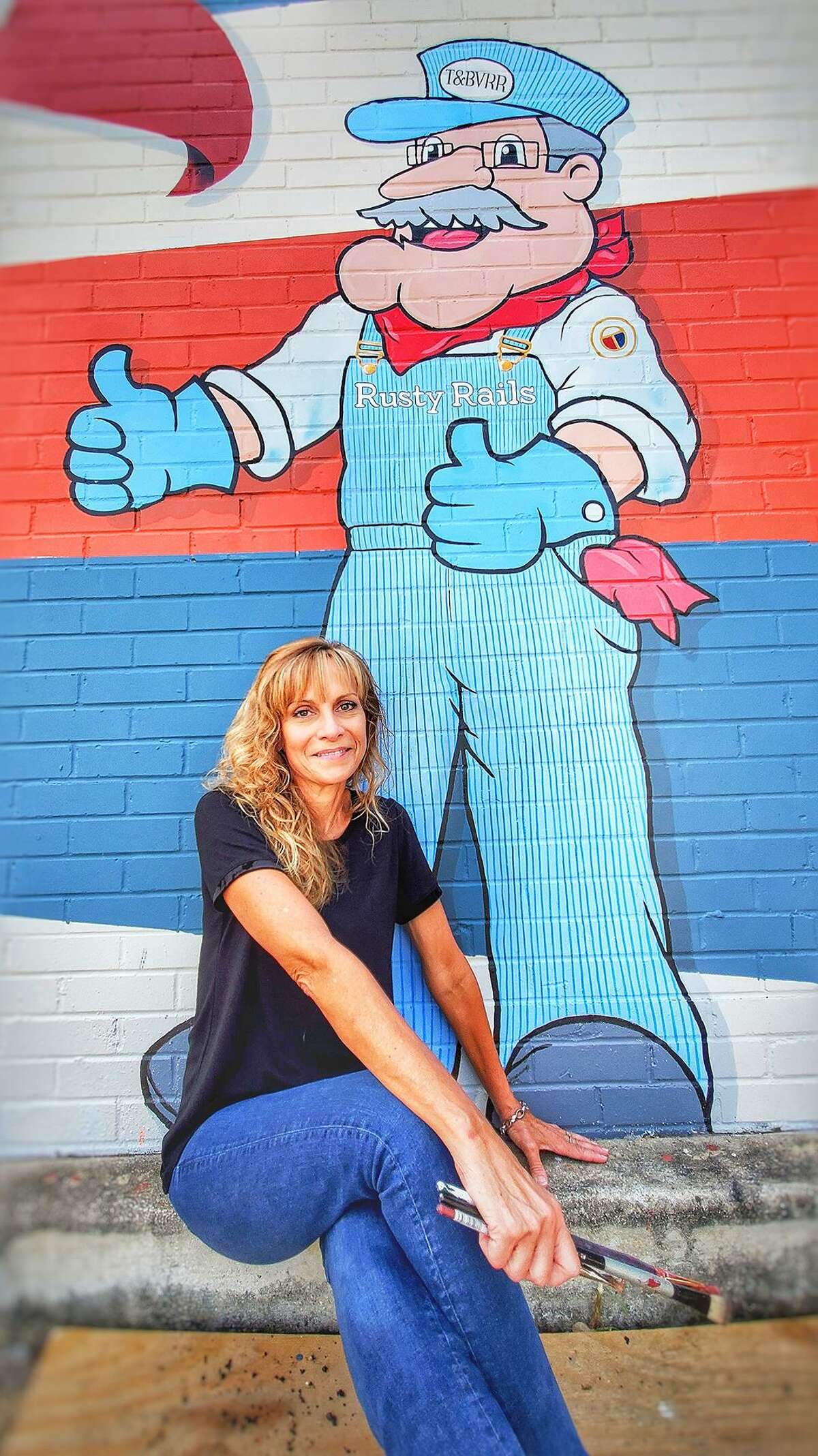 Artist Beth Mankin takes a break for a quick selfie with Tomball mascot Rusty Nails. Mankin was a contributor to the development of the mascot's brand for the city.