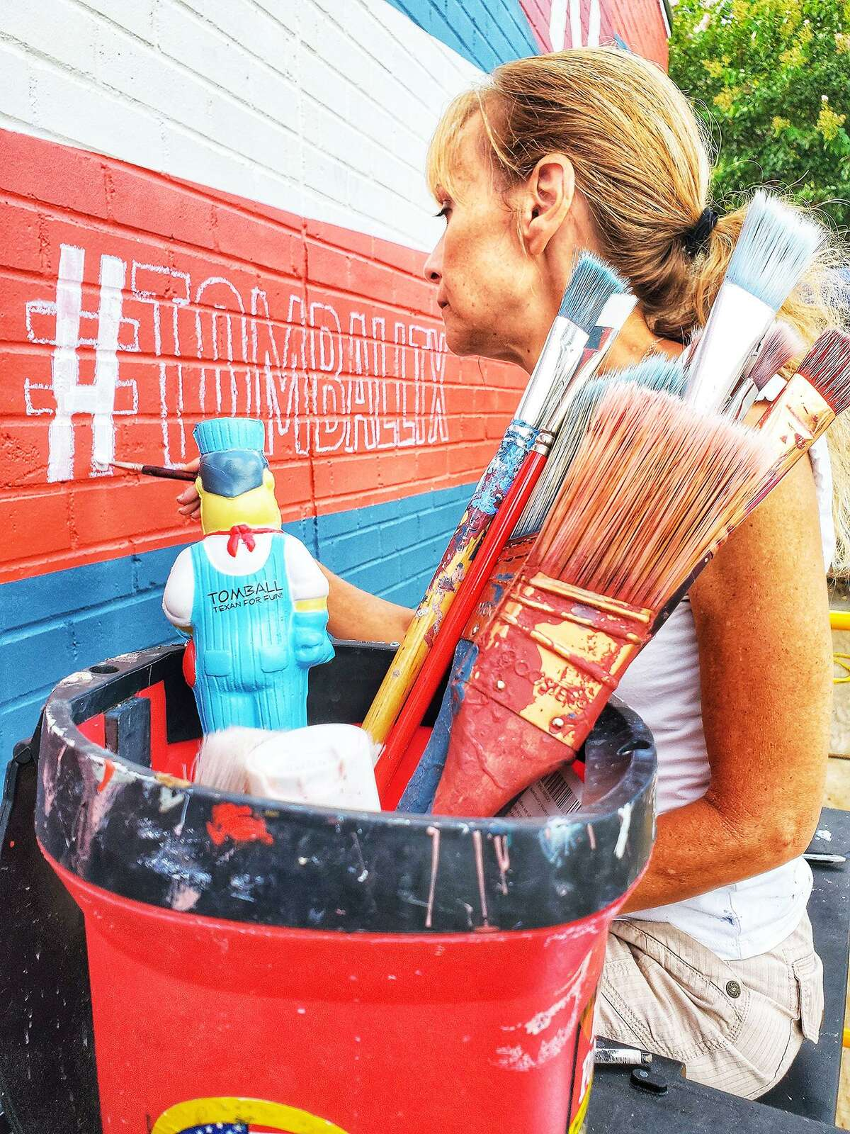 A stuffed Rusty Nails doll looks on as artist Beth Mankin paints on the lettering for the new mural for the city of Tomball. The wall is located at 214 W. Main at the Tomball Tourism and Marketing office.