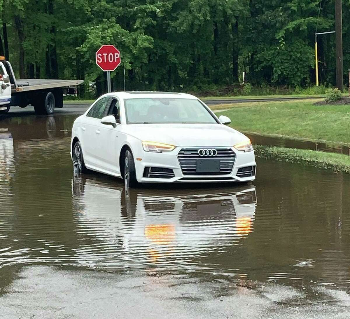 An Audi was stuck in a water and stalled in South Windsor, Conn., on Thursday, Aug. 19, 2021. He said an officer was able to pull up next to the woman's car and have her climb into the backseat of the cruiser before the water levels got too high.