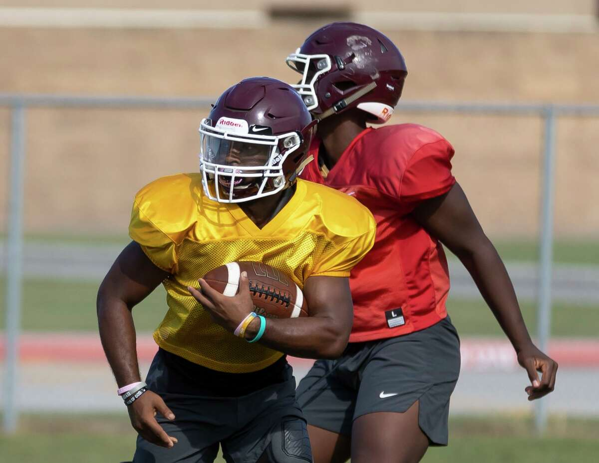 Summer Creek running back Torrie Curry, left, pushes through the defensive during football practice at Summer Creek High School, Wednesday, Aug. 11, 2021, in Houston.