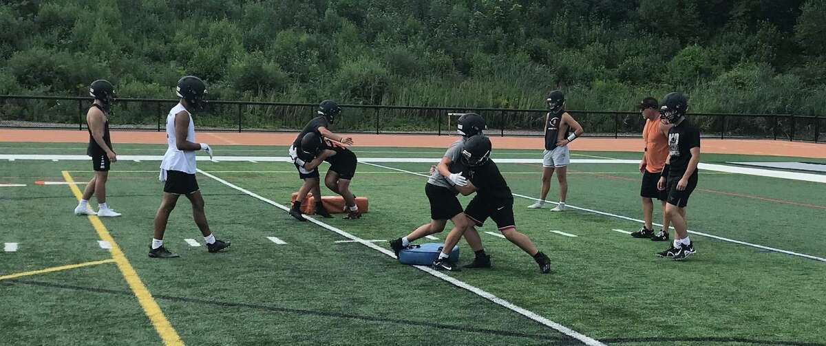 Shelton defensive coordinator Dan Dunaj works on proper tackling techniques.