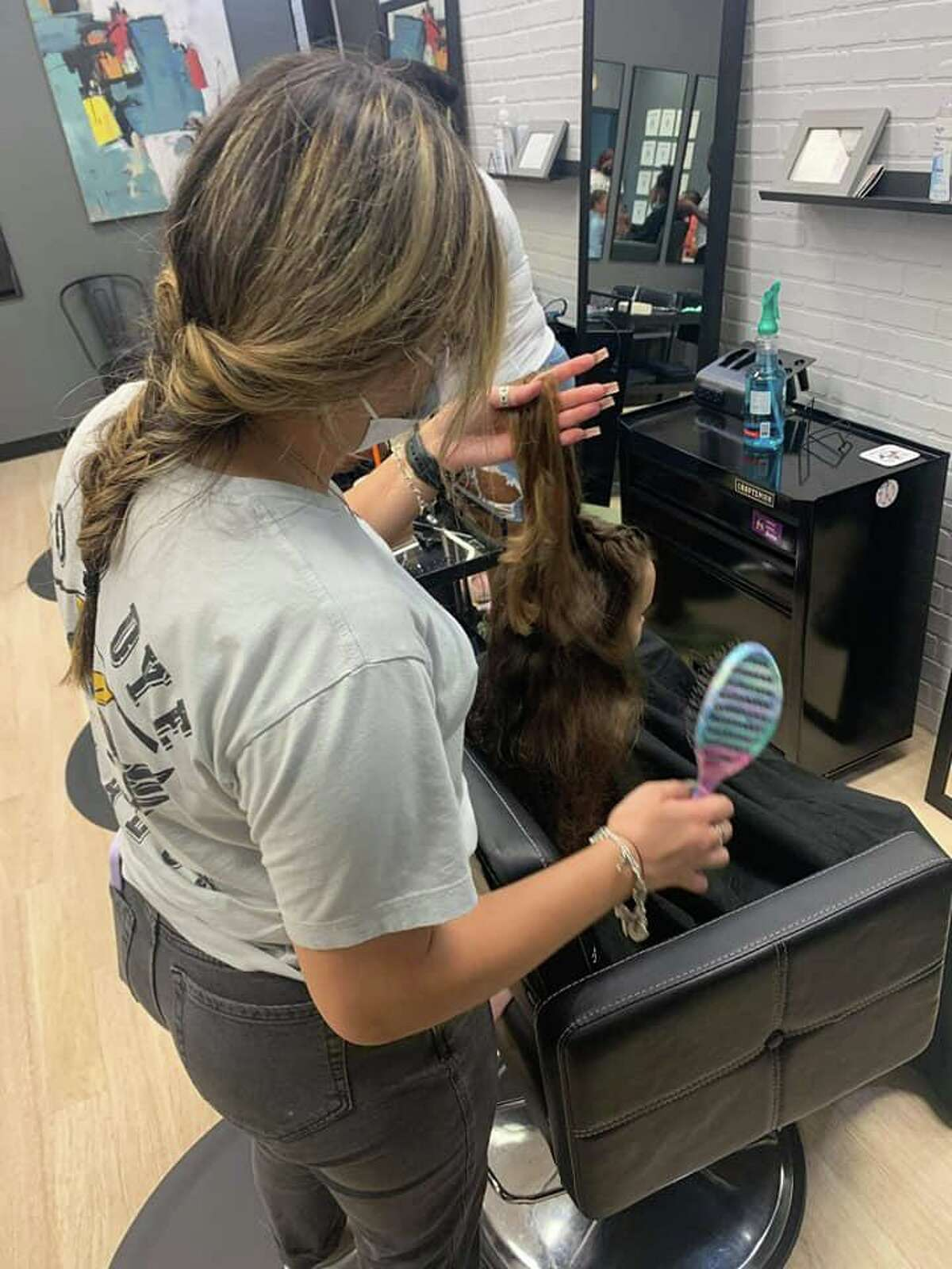 Dozens of fades, tapers, braids and trims for boys and girls were performed by the staff, including Kane's wife, Olivia who owns the adjoining salon and spa, Do or Dye.
