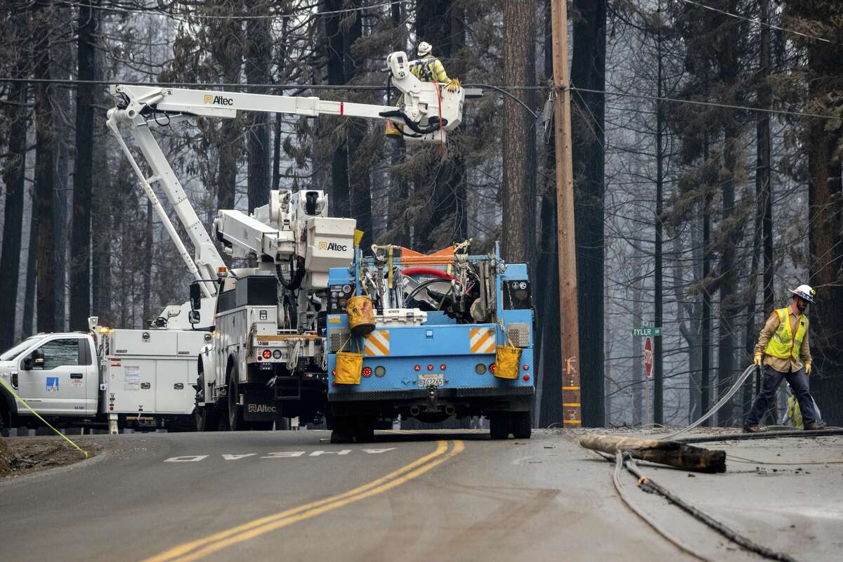 FILE: Pacific Gas and Electric employees clear downed power lines on Sciaroni Road, Wednesday, Aug. 18, 2021, Grizzly Flats, Calif., after the Caldor Fire burned through the area.