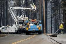 Pacific Gas and Electric employees clear downed power lines on Sciaroni Road, Wednesday, Aug. 18, 2021, Grizzly Flats, Calif., after the Caldor Fire burned through the area.