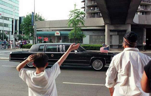1996: Onlookers watch and wave as President Bill Clinton's motorcade passes St. John's Towers at the corner of Washington Blvd. and Tresser Blvd. in Stamford. Photo: File Photo / Stamford Advocate File Photo
