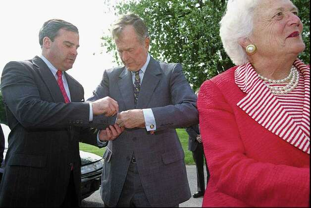 1998: Former President George Bush, middle, receives some help with his cufflink from Connecticut Governor John Rowland, left, while Barbara Bush, the former First Lady greets guests at the Belle Haven Yacht Club in Greenwich. Photo: File Photo / Stamford Advocate File Photo