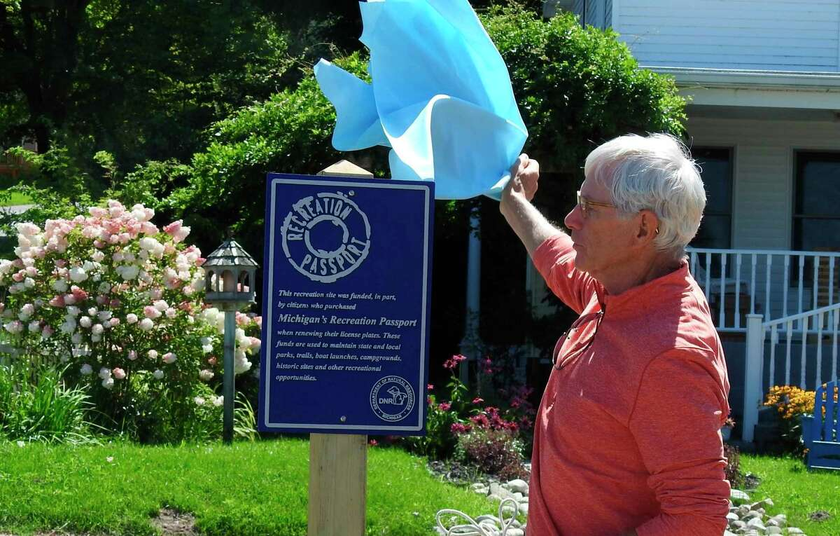 Jed Maker, board president of the Friends of the Betsie Valley Trail, unveils a sign recognizing the Department of Natural Resource's Recreation Passport Grant used to help resurface a worn portion of the trail along Crystal Lake. (Courtesy Photo)