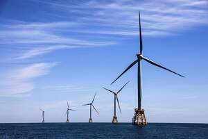 Wind turbines stand tall off the coast of Rhode Island. Obama-era incentives and investments in renewable energy are paying off as the price for wind and solar falls dramatically.