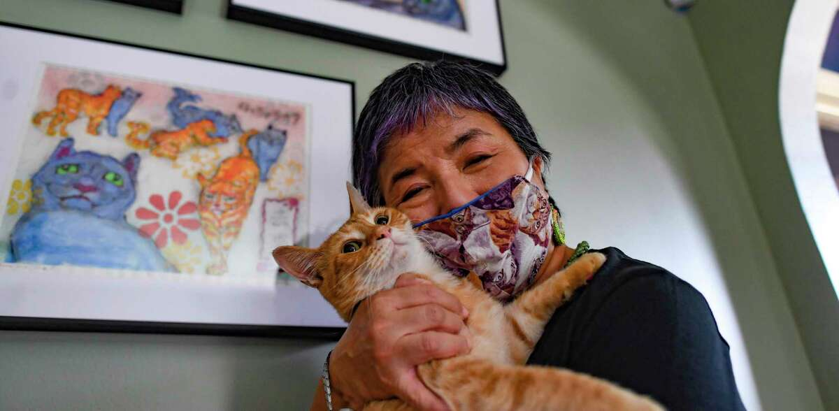 Yoko Misu embraces her cat Tora, who is the subject of much of her recent art.