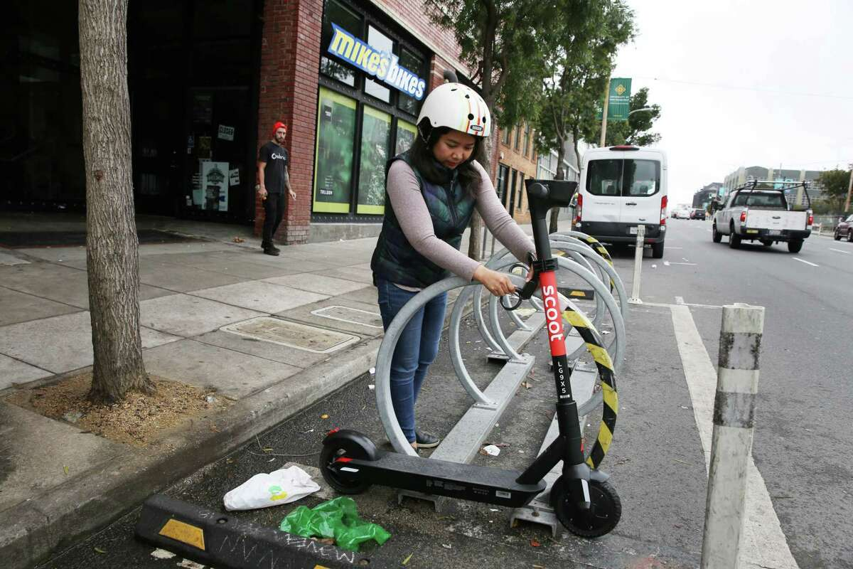 Emily Calangian, a Scoot accountant, demonstrates how to lock a Bird scooter in San Francisco.