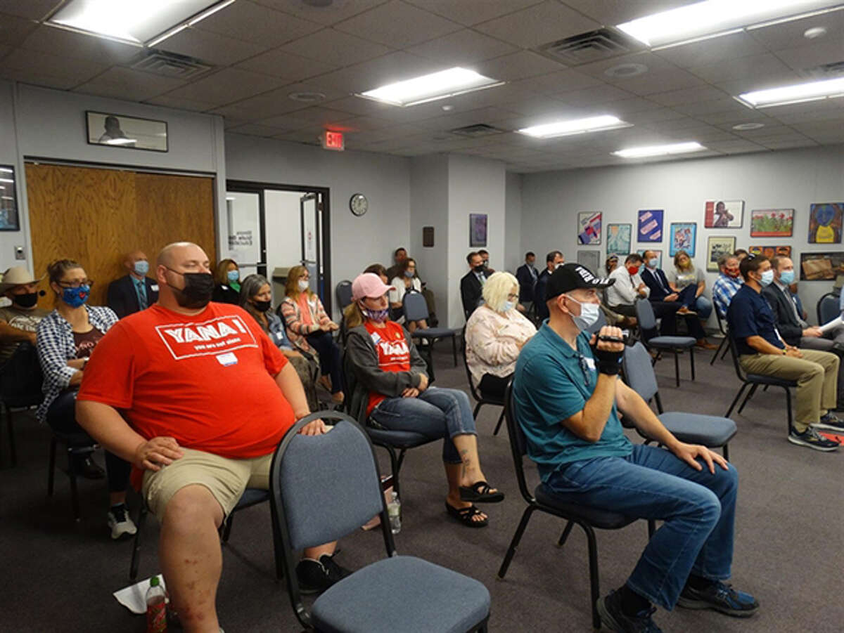Dozens of people crowd into the Illinois State Board of Education meeting Wednesday in Springfield to protest a universal mask mandate now in place for all public and nonpublic schools in the state.