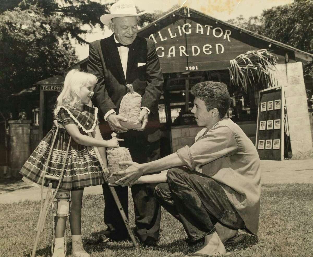 A young Richard Kimbrell, right, is shown with Helen McDonald, left, and Dan Quill at Alligator Garden. Coins retrieved from one of the 10 gator enclosures were donated to benefit children with polio.