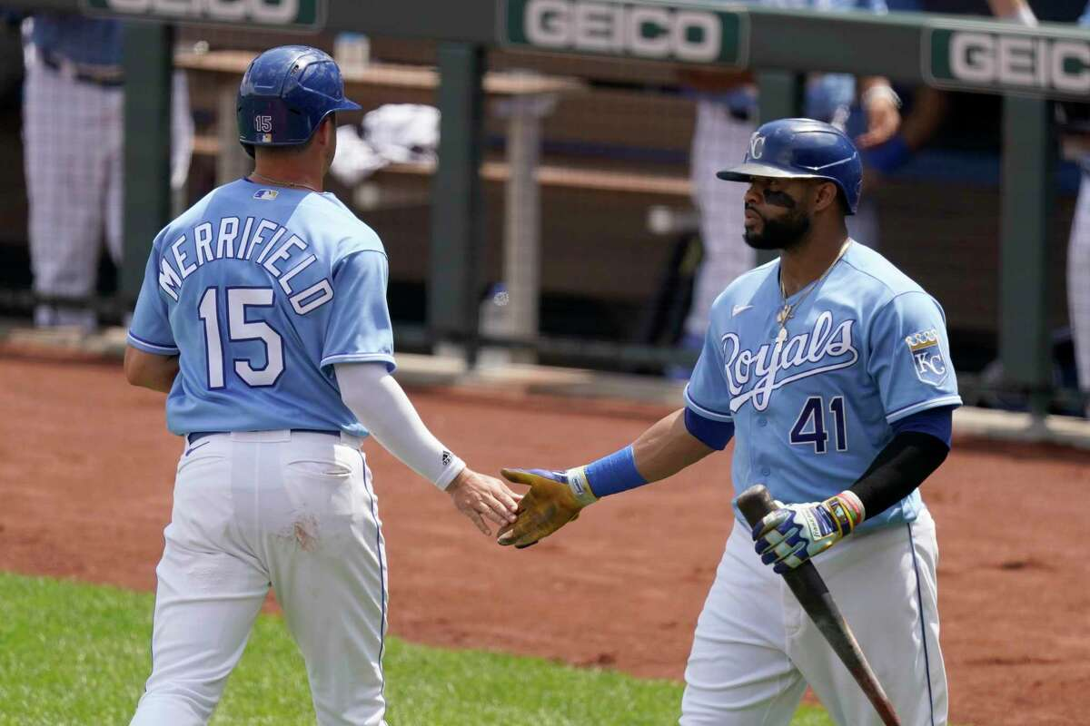 Kansas City Royals' Whit Merrifield (15) celebrates with Carlos Santana (41) after scoring on a sacrifice fly hit by Salvador Perez during the first inning of a baseball game against the Houston Astros Thursday, Aug. 19, 2021, in Kansas City, Mo. (AP Photo/Charlie Riedel)
