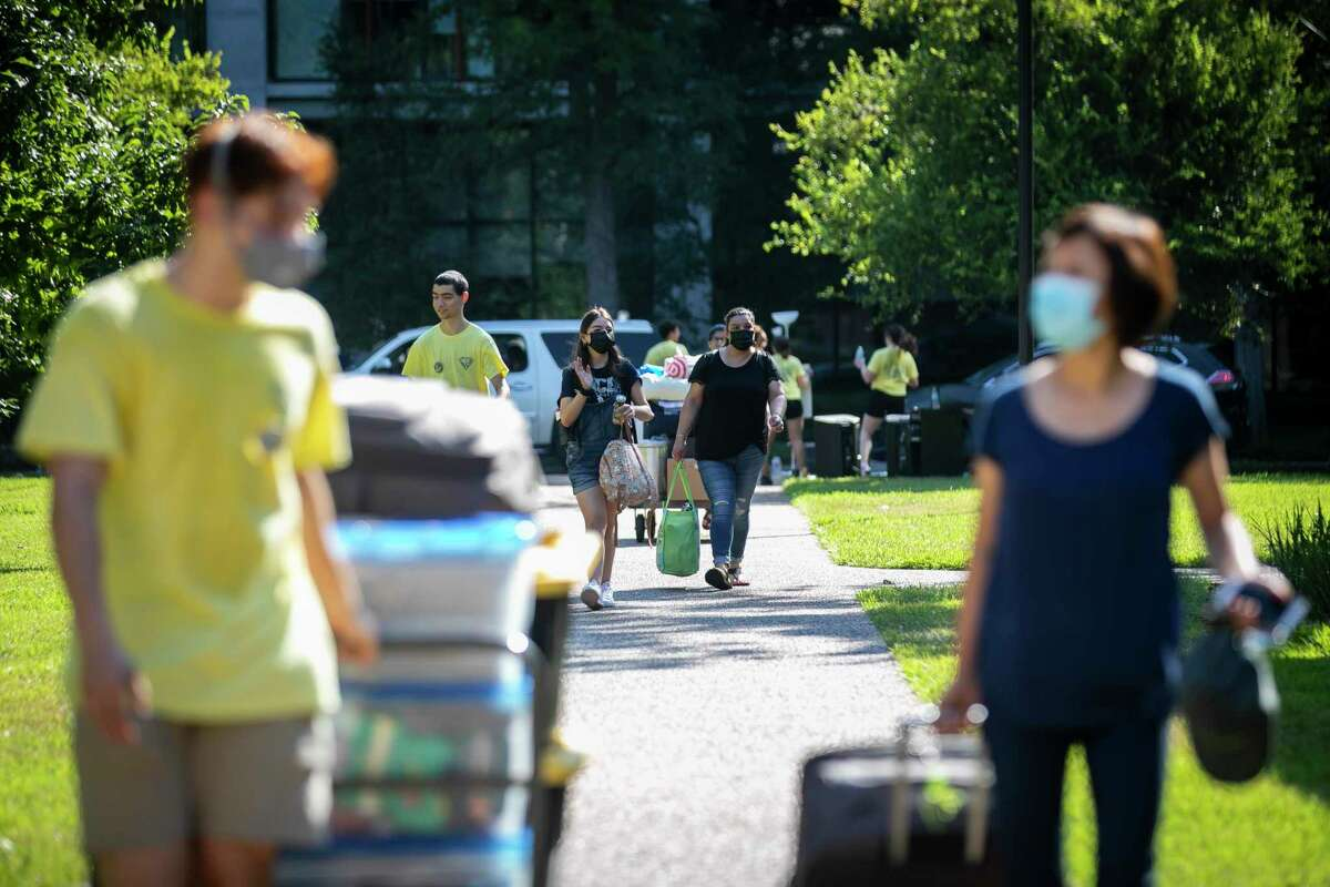 Students and their familes carry their belongings into dorms during move-in at Rice University Sunday, Aug. 15, 2021.