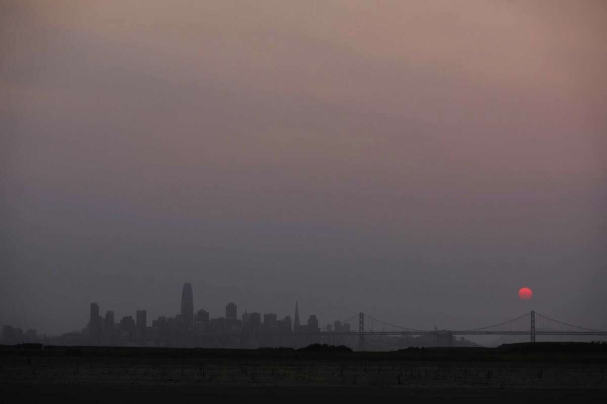 An orange sun sets in a hazy San Francisco skyline seen from Alameda. Bay Area residents have been urged to stay inside to avoid unhealthy air and smoke from Northern California wildfires.