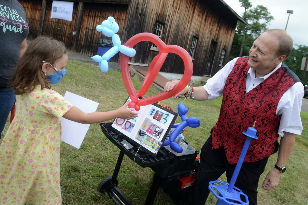 Chelsea Brelsford, age 6, receives a balloon from magician Bryant Lizotte during a season ending event for Mayor Laura Hoydick's Summer Reading Challenge, in Stratford, Conn. Aug. 18, 2021.