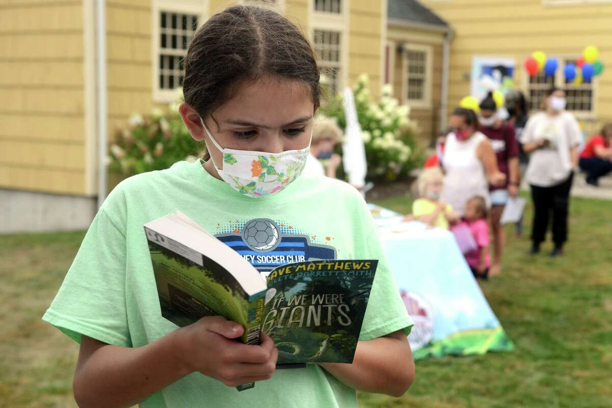 Julianne Gonzalez browses one of the books available during a season ending event for Mayor Laura Hoydick's Summer Reading Challenge, in Stratford, Conn. Aug. 18, 2021.