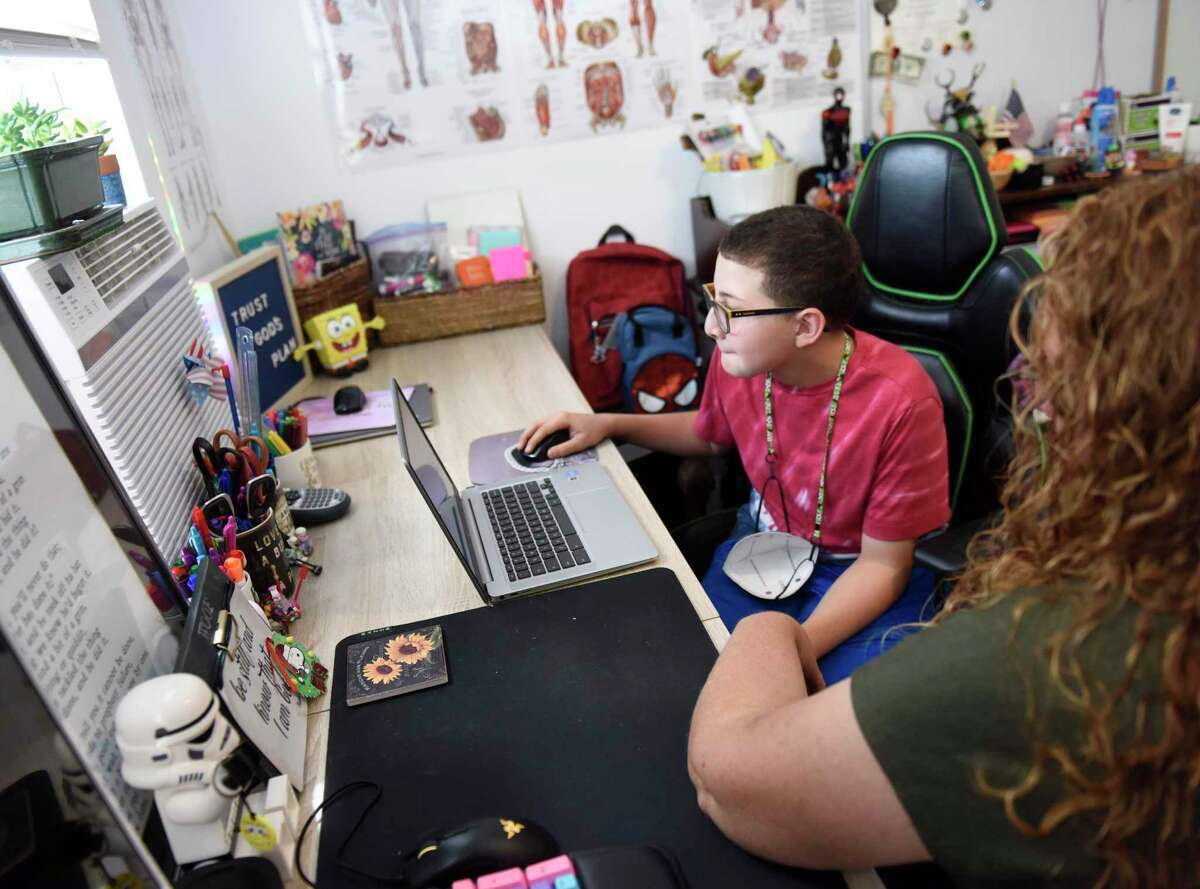 Isaac Lopez, 11, uses his laptop with his mother, Jodi Clark-Lopez, at their home in Stamford, Conn. Monday, Aug. 16, 2021. Stamford has announced that it would not offer remote learning for the upcoming school year, so Clark-Lopez started a change.org petition calling on Stamford schools to offer a remote option in the fall.