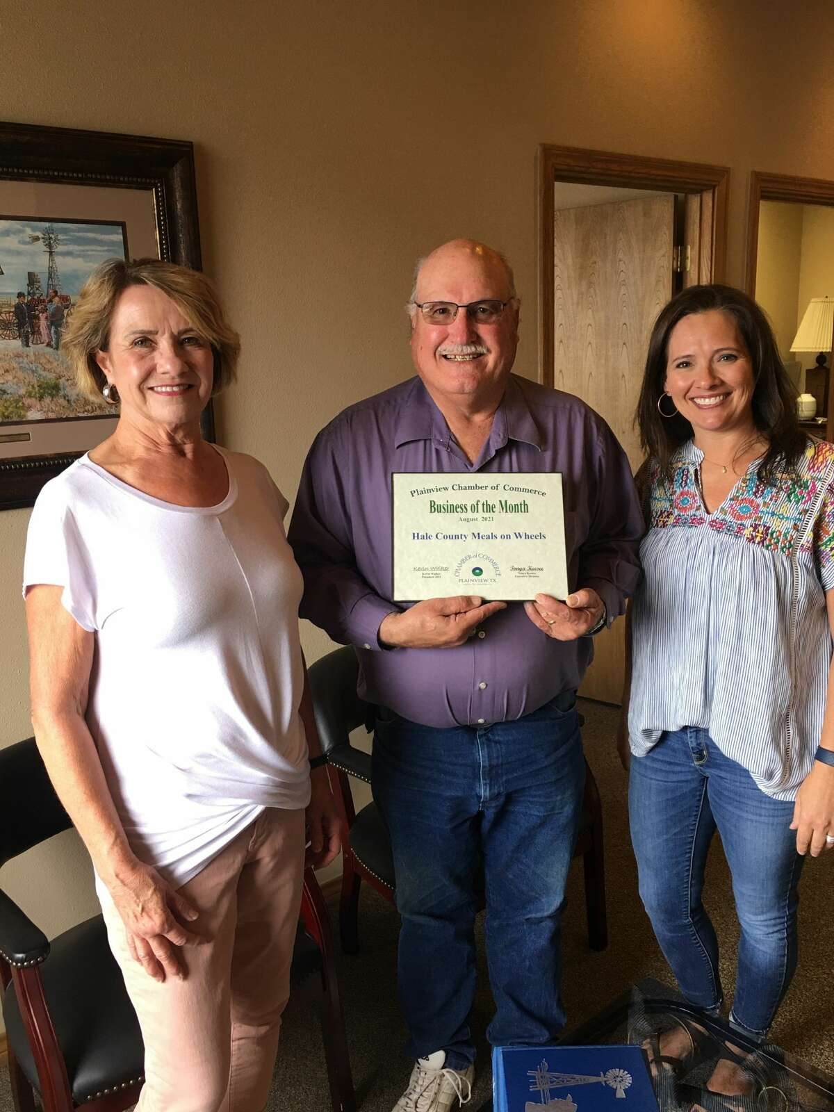 Executive Director Kim Horne, Board President Doug McDonough and Assistant Director Ashley Mayberry accept the Chamber's Business of the Month recognition for August.