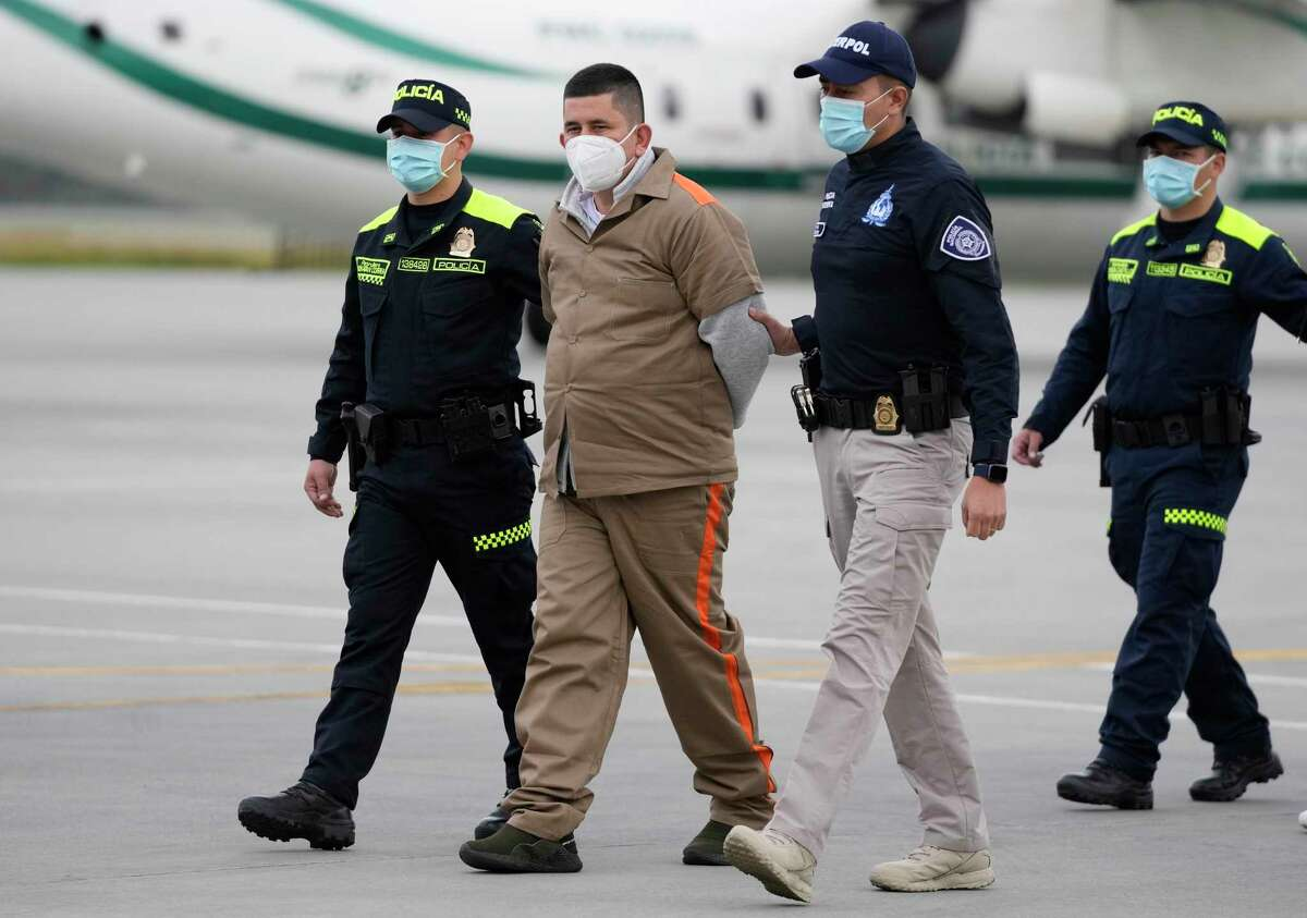 Henry Trigos Celon, a member of Colombian National Liberation Army, is escorted by police prior to his extradition to the U.S at the CATAM military airport in Bogota, Colombia, Thursday, Aug. 19, 2021. Celon is wanted in Texas on charges related to drug trafficking. (AP Photo/Fernando Vergara)