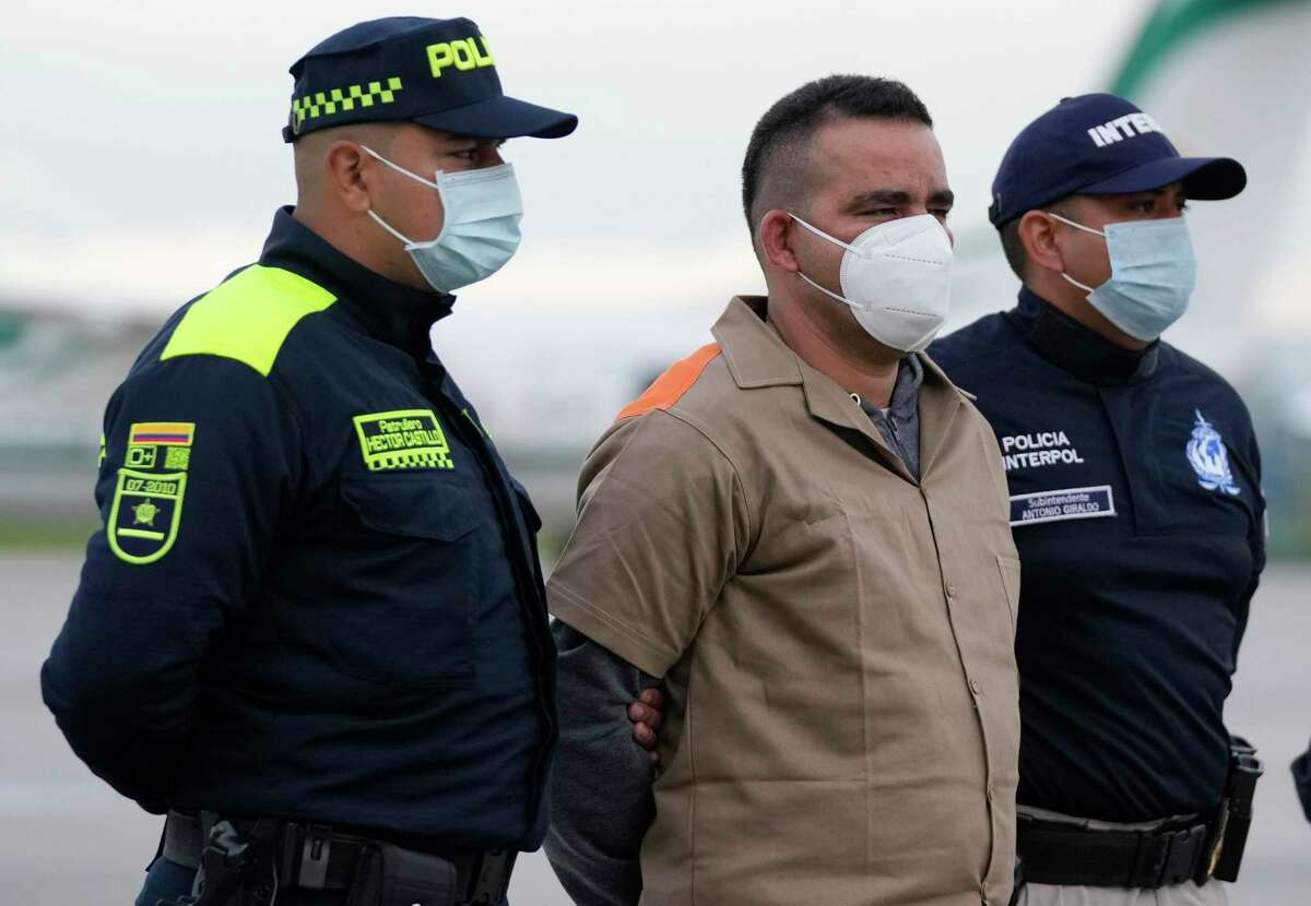 Yamit Picon Rodriguez, a member of Colombian National Liberation Army, is escorted by police prior to his extradition to the U.S, at the CATAM military airport in Bogota, Colombia, Thursday, Aug. 19, 2021. Rodriguez is wanted in Texas on charges related to drug trafficking. (AP Photo/Fernando Vergara)