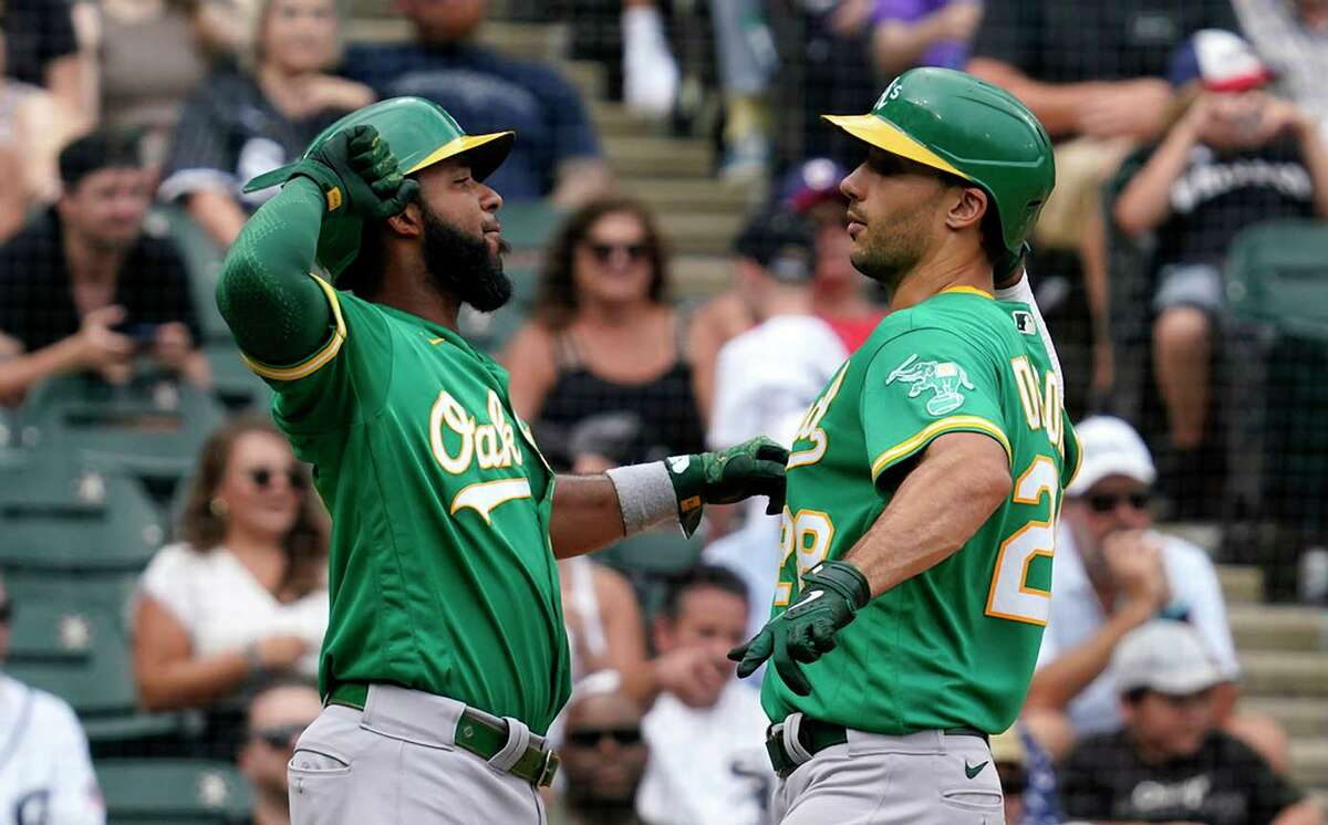 Matt Olson (28) and Elvis Andrus celebrate Olson's two-run home run in the seventh inning in Chicago. The blast snapped a 3-3 tie, helping the A's avoid a four-game sweep by the White Sox.