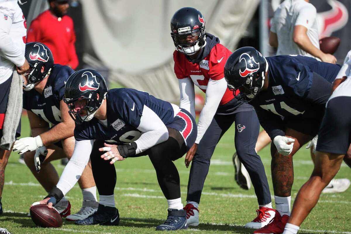 Houston Texans quarterback Tyrod Taylor (5) lines up under center Justin Britt (68) during an NFL training camp football practice Thursday, Aug. 19, 2021, in Houston.